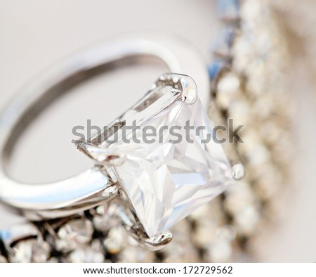 Close up detail view of a choice of quality female jewelery laying together on a white background and shining ring, bracelet and necklace. Luxury fashion jewels engagement ring. - stock photo