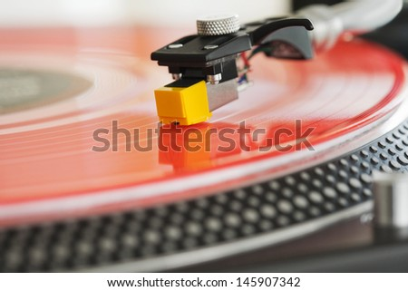 Close up detail view of a dj turntable deck and needle playing music on a red vinyl disc in a nightclub. - stock photo