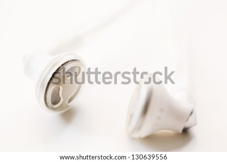Close up detail view of a pair of musical earphones laying together, isolated on a white background. - stock photo