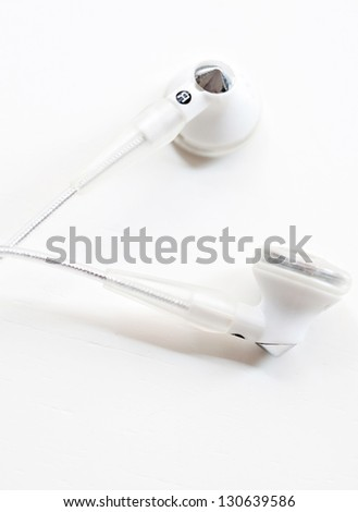 Close up detail view of a pair of musical earphones laying together on a white background. - stock photo