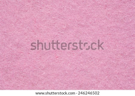 Close up detail view of a pink piece of textured felt fabric with rough touch. Full frame background texture pattern of art and stationery material in magenta color. - stock photo