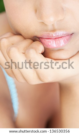 Close up detail view of a young african american girl lips and chin leaning on her hand while relaxing.