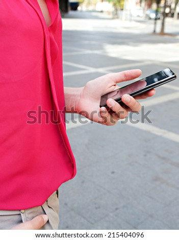Close up detail view of a young professional business woman hand holding a modern smartphone mobile phone while standing in a city street during a sunny day. Technology working outdoors. - stock photo