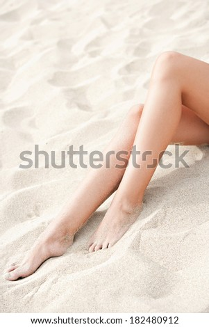 Close up detail view of an attractive woman pair of bare legs relaxing on the dunes of a white sand beach, sunbathing on holiday. Healthy well being lifestyle and travel.