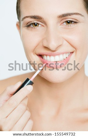 Close up detail view of an attractive young woman applying pink glossy lipstick while joyfully smiling at the camera against a white background, indoors. - stock photo