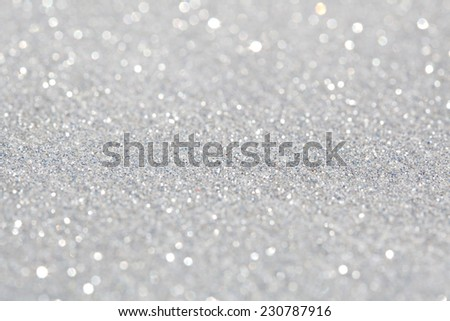 Close up detail view of silver glitter background shining and reflecting light and showing stars. Full frame glitter texture. Party, celebration, abstract and festive background textures. - stock photo