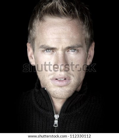 Close-up detailed portrait of young good looking male model against black background - stock photo
