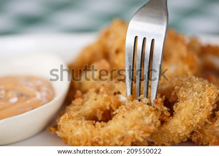 Close-up dish of fried squid ring with fork served with sweet sauce - stock photo