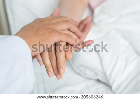 Close-up doctor holding hand of the patient - stock photo