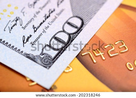 Close-up dollar note on credit card with shallow depth of field - stock photo