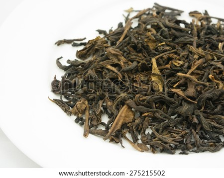 Close up dried earl grey tea leaves on white plate - stock photo