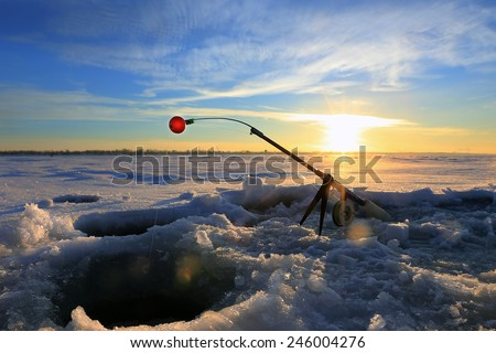 close-up drill, fishing rod near the hole on the ice in winter river at sunset - stock photo