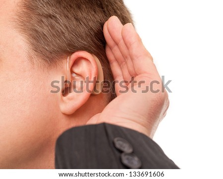Close up ear of a middle aged businessman wearing hearing aid and listening for a sound. - stock photo