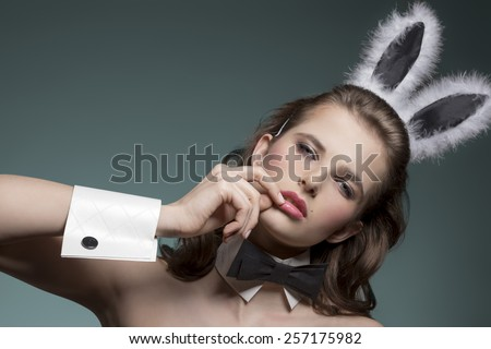 close-up easter portrait of sexy brunette girl with fluffy bunny ears and black papillon, looking in camera  - stock photo