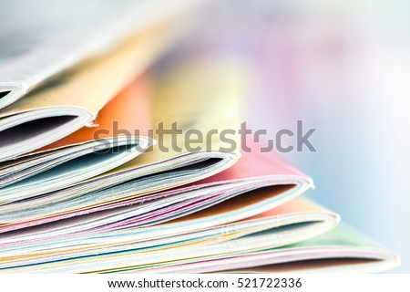 Close up edge of colorful magazine stacking with  blurry bookshelf background for bublication and publishing concept , extremely shallow DOF
