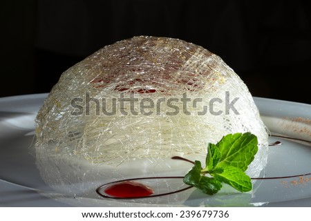 close-up elegant dessert flame cheesecake on a white plate decorated with mint leaves and jam - stock photo