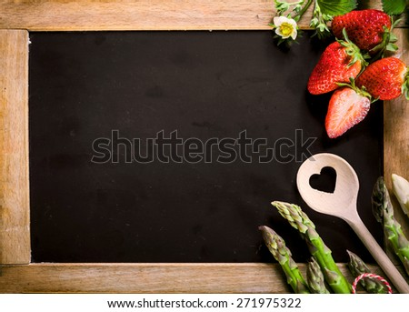 Close up Empty Black Chalkboard with Asparagus, Berries and Ladle on the Right Edge, Emphasizing Copy Space for Texts. - stock photo