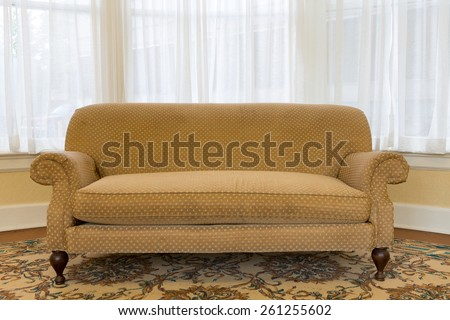 Close up Empty Elegant Brown Couch Furniture at the Living Area with White Curtains to Glass Windows on the Background. - stock photo