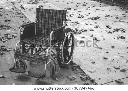 Close up empty wheelchair in pathway of park, Black and White concept, lonely