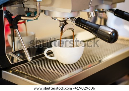 Close up espresso preparing in white ceramic cup from automatic coffee maker machine