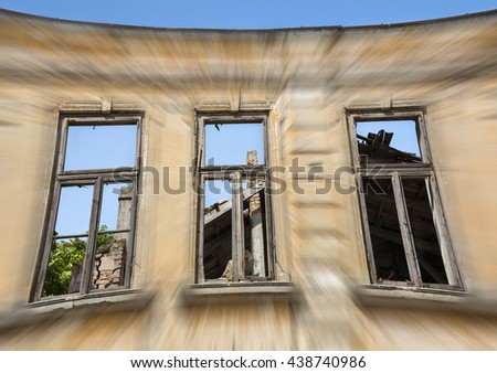 Close up - exterior facade of abandoned house with old wooden windows . Motion blur composition. - stock photo