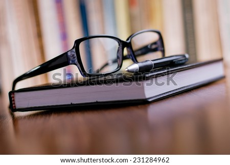 Close up Eyeglasses with Black Frame and Black Ballpoint Pen on Top of the Book at the Office Table. - stock photo