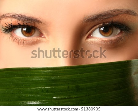 close-up eyes and green leaf - stock photo