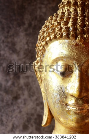 close up face golden buddha in the dark