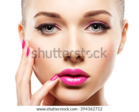 Close-up face of a beautiful  girl with pink eye makeup and  pink  nails. Fashion model posing on white background