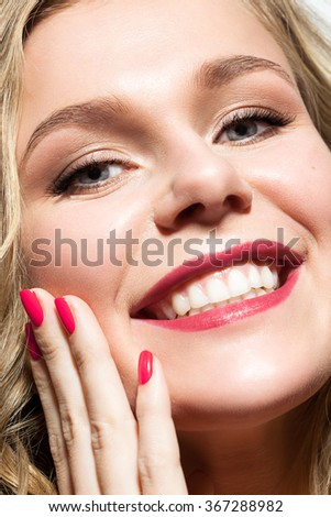 Close-up face of a girl with a toothy smile and a red nail polish