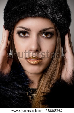 Close up Face of a Gorgeous Woman with Gold Lips Make up Wearing Furry Black Winter Fashion with Both Hands on the Hat and Looking at the Camera. Captured in Studio on a Gray background. - stock photo