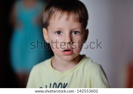 Close-up face of a little boy in a yellow jacket - stock photo