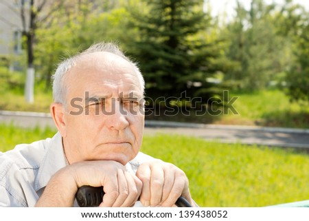 Close up face of an old man over the park background - stock photo