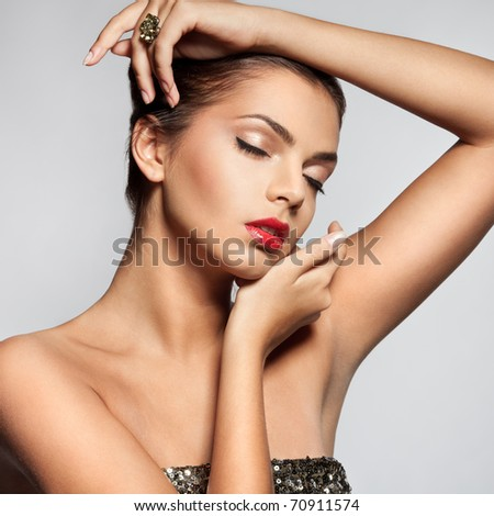 Close-up face of beautiful caucasian brunet woman with ring. Studio shot