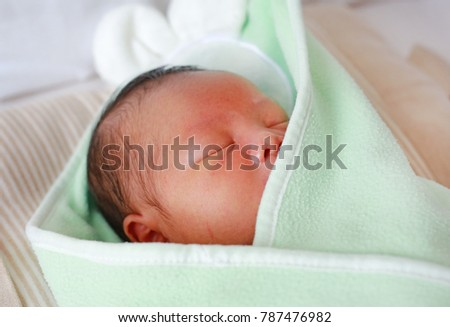 Close-up face of newborn Asian baby in the blanket.