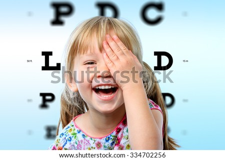 Close up face portrait of happy girl having fun at vision test.Conceptual image with girl closing one eye with hand and block letter eye chart in background. - stock photo