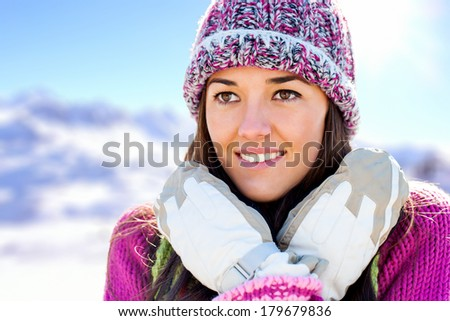 Close up face shot of attractive girl wearing beanie and gloves in snowy mountains.