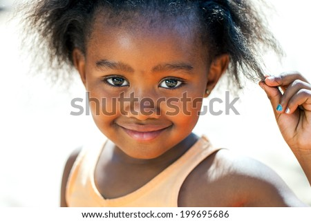 Close up face shot of cute African girl touching hair.