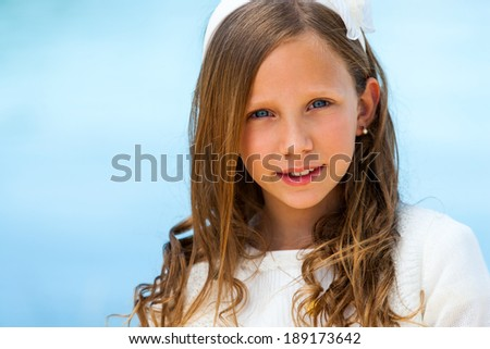 Close up face shot of cute communion girl against blue background.  - stock photo