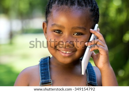 Close up face shot of cute little african girl talking on smart phone against green outdoor background. - stock photo