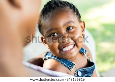 Close up Face shot of little african girl laughing. Child looking at out of focus mother. - stock photo
