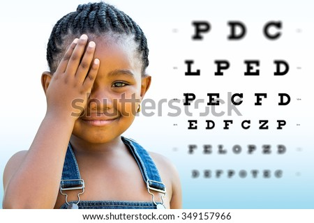 Close up Face shot of little African girl testing vision. Girl with braided hairstyle closing on eye with hand. Vision chart with block letters and focus point in background.