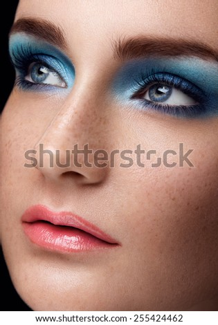 Close up facial beauty portrait of girl face, pink lipstick, blue eyeshadows  on black background - stock photo