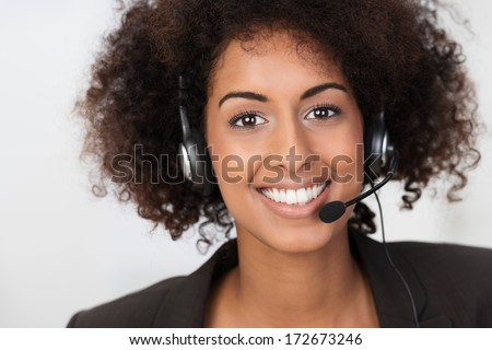 Close up facial portrait of a beautiful vivacious African American businesswoman wearing a headset smiling at the camera conceptual of client services, support or a call centre operator - stock photo