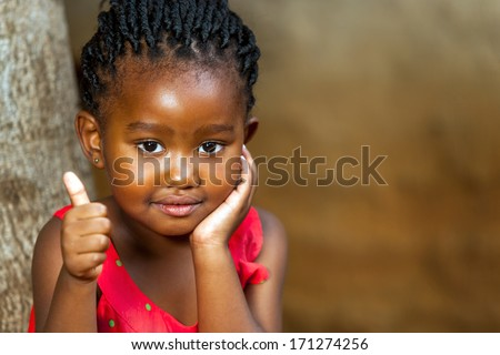 Close up facial portrait of african girl doing thumbs up outdoors. - stock photo