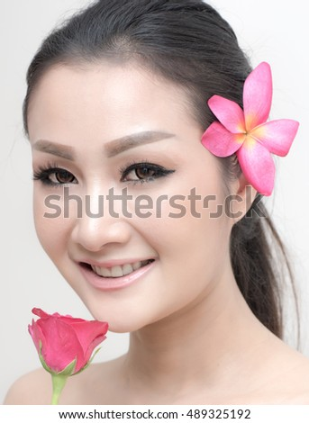 Close-up facial portrait of smiling asian girl with healthy skin holding a rose close to her face on white background