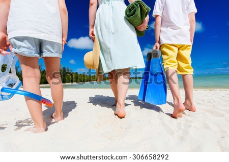 Close up family of mother and kids with towel and snorkeling equipment enjoying vacation at tropical beach - stock photo
