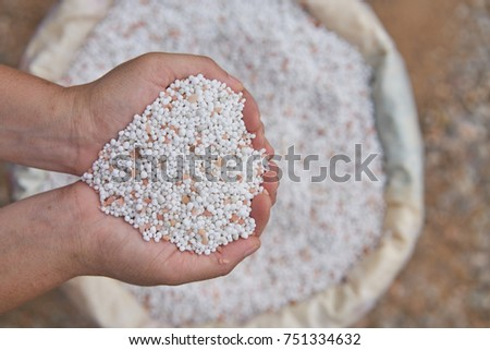 close up farmer woman hand hold chemical Fertilizer over fertilizer sacks.