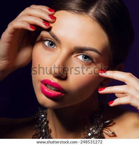 Close up fashion beauty portrait of glamour  woman with  red  full lips , colorful nails and perfect skin , Evening make up. Posing against black background in studio. Wearing  effect necklace. - stock photo