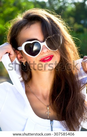 Close up fashion bright portrait of young woman with amazing brunette hair and nice make up, smiling and walking in the park, outdoor. Young girl wearing white hoodie and heart shaped sunglasses. - stock photo